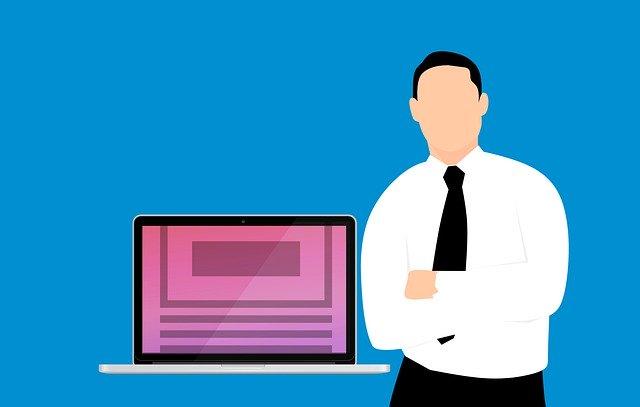 muž stojící vedle počítače s fialovým displejem