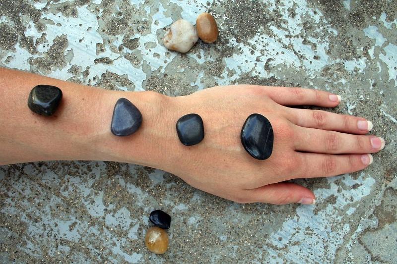 ruka s lávovými kameny